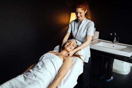 Massage therapist massaging woman