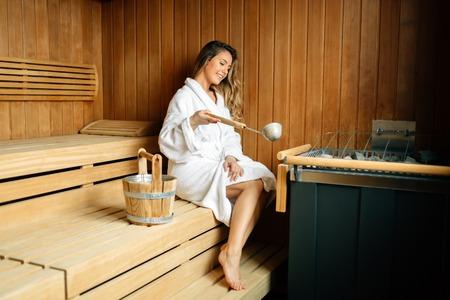 Bella mujer sentada en la sauna finlandesa