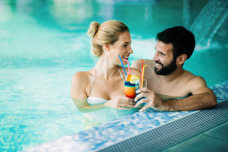 Happy attractive couple relaxing in swimming pool