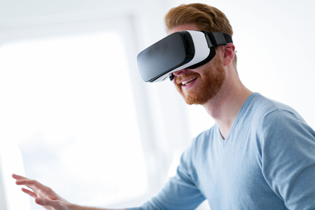 Young handsome man trying virtual reality glasses