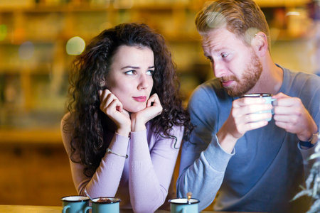 Young attractive couple having problems on date