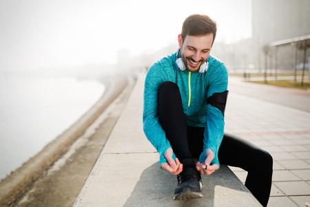 Man tying jogging shoes. Person running outdoors Stock fotó