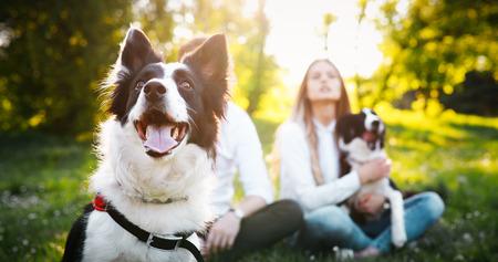 Feliz pareja romántica enamorada disfrutando de su tiempo con mascotas en la naturaleza