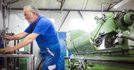 Industrial metal worker working on metal components in factory