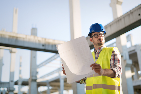 Portrait of male site contractor engineer with hard hat holding blue print paper at construction site,
