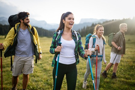 Hiking with friends is so fun. Group of young people with backpacks walking together Stockfoto