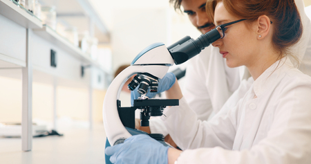 Young scientist looking through microscope in laboratory Stock Photo