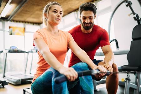 Mujer hermosa joven haciendo ejercicios con entrenador personal