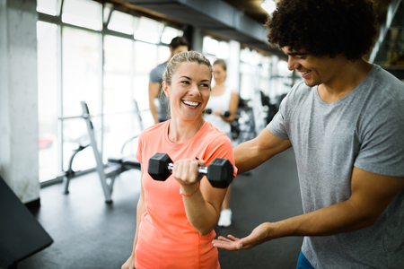 Young beautiful woman doing exercises with personal trainer 写真素材