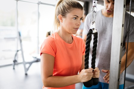 Young beautiful woman doing exercises with personal trainer Stock Photo