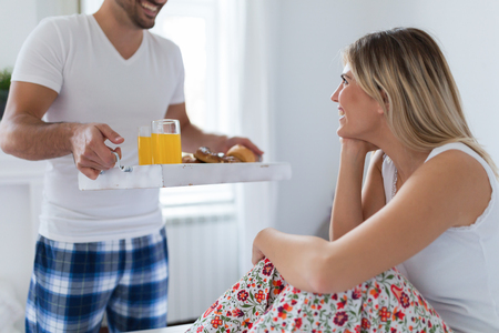 Young attractive couple having breakfast in bed Stockfoto