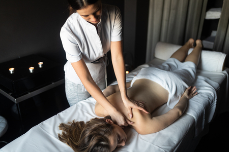 Young and healthy woman in spa salon. Traditional Swedish massage therapy Standard-Bild