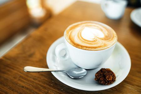 Beker met warme lekkere koffie op houten tafel in café, close-up Stockfoto