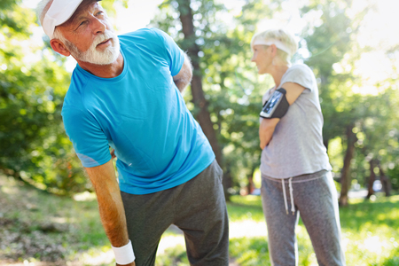 Mature man having a back pain during jogging Stock Photo