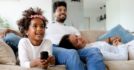 Young girl watching tv with her parents Banco de Imagens