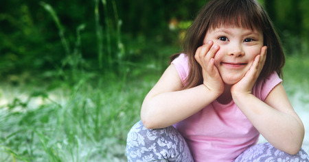 Portrait of beautiful little girl with down syndrome