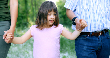 Beautiful little girl with down syndrome walking with parents Foto de archivo - 111441348