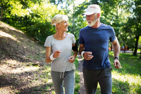Mature couple jogging and running outdoors in city Stock Photo