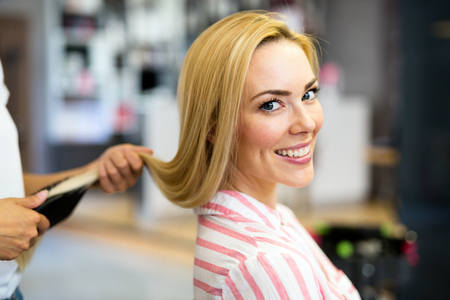 Happy young woman and hairdresser with fan making hot styling Stock Photo