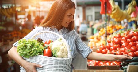 Mooie gelukkige vrouwen die groenten en fruit winkelen Stockfoto