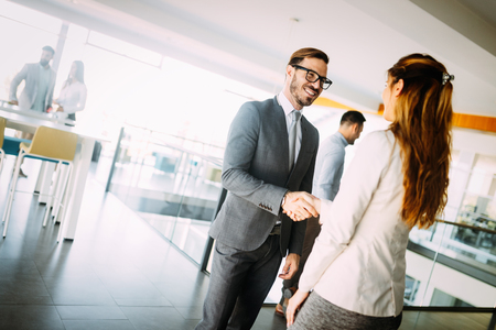 Young businessman and woman shake hands as hello in office portrait Reklamní fotografie
