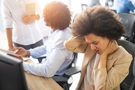 Young african business woman having stress and headache in the office