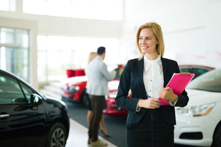Professional saleswoman working in car dealership