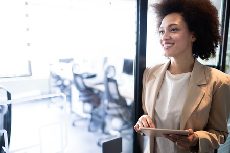 Portrait of an attractive young african businesswoman smiling while standing by windows in office