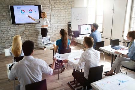Erfolgreiche glückliche Gruppe von Menschen, die während der Präsentation Software Engineering und Business lernen