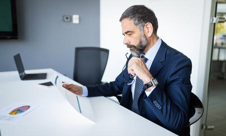 Selbstbewusster leitender Geschäftsmann, der im Büro arbeitet working