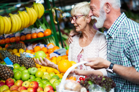 Senior family couple choosing bio food fruit and vegetable on the market during weekly shopping 스톡 콘텐츠