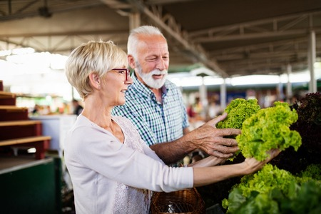 Senior family couple choosing bio food fruit and vegetable on the market during weekly shopping Reklamní fotografie