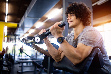 Young fit handsome man doing exercises in gym 스톡 콘텐츠