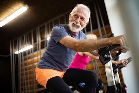 Colocar pareja madura haciendo ejercicio en el gimnasio para mantenerse saludable Foto de archivo