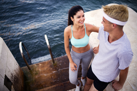 Runners training together. Man and woman joggers exercising outdoors.