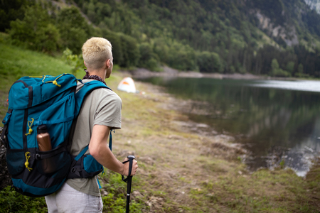 Young man traveling with backpack hiking in mountains Stock fotó