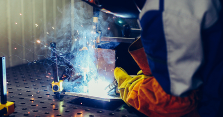 Worker welds at the factory working in metal industry 版權商用圖片