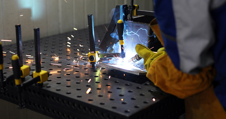Worker cutting metalsheet by torch with bright sparks in fabication factory Фото со стока