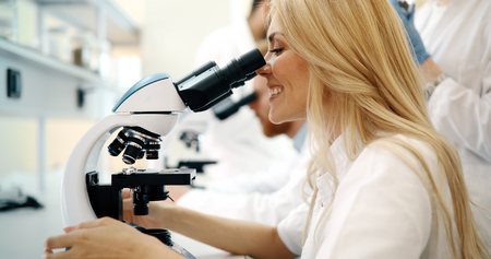 Young scientist looking through microscope in laboratory Stock fotó
