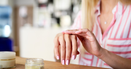 Woman applying moisturizing cream on hands Standard-Bild