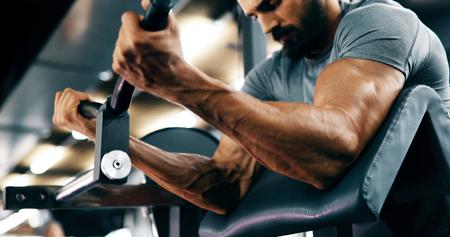Entschlossener hübscher und junger Mann, der im Fitnessstudio trainiert Standard-Bild