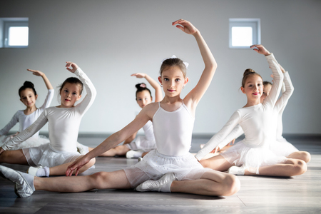 Group of little ballerinas girls doing exercises in dance school