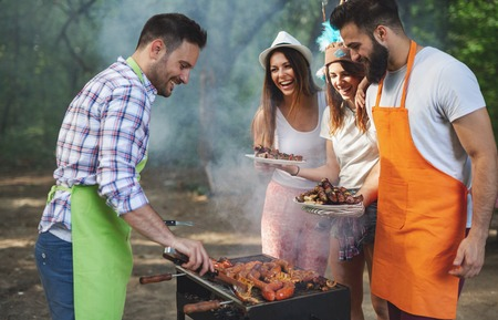 Group of friends having a barbecue and grill party in nature Stock Photo