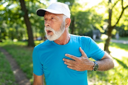 Senior man with chest pain suffering from heart attack during jogging Stock Photo
