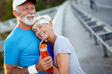 Healthy senior, couple jogging in the city at early morning with sunrise