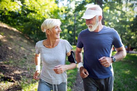 Glückliches fittes älteres Paar, das im Park trainiert Standard-Bild