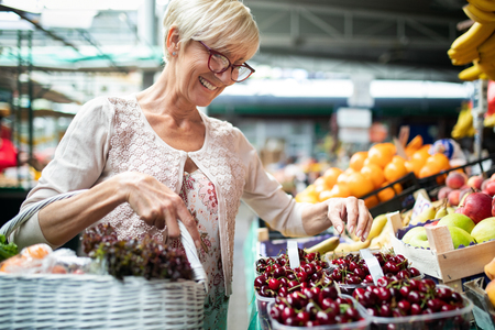 Senior woman buying fresh fruits and vegetables at the local market Stock Photo