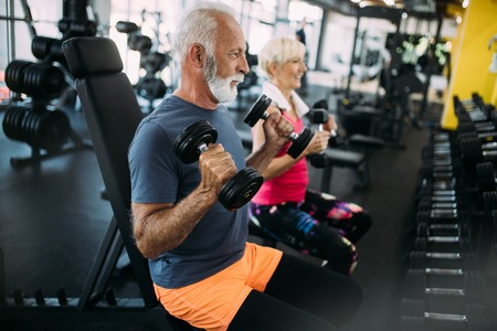 Happy senior people doing exercises in gym to stay fit Stockfoto