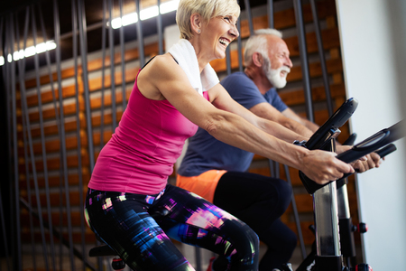 Mature fit people biking in the gym, exercising legs doing cardio workout cycling bikes 免版税图像