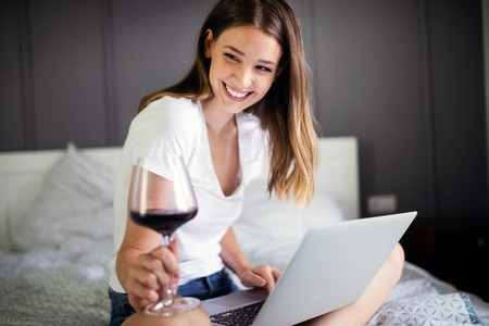 Young woman using her laptop while relaxing on bed and drinking wine
